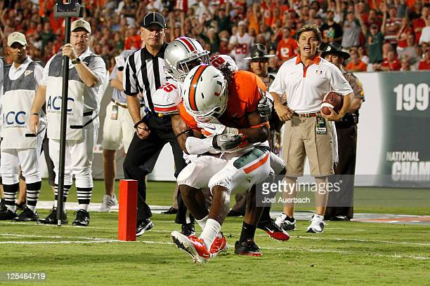 Allen Hurns of the Miami Hurricanes catches his second touchdown pass of the first quarter while being tackled by Bradley Roby of the Ohio State...