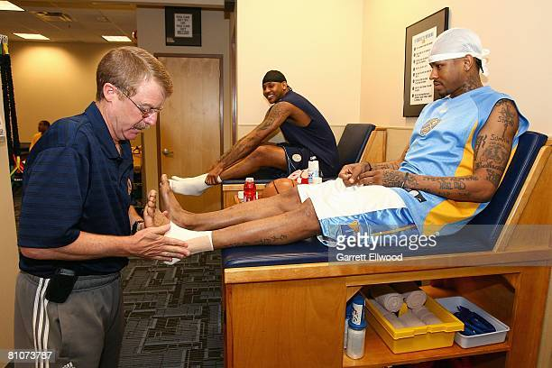 Allen Iverson and Carmelo Anthony of the Denver Nuggets get their ankles taped by athletic trainer Jim Gillen before Game Three of the Western...