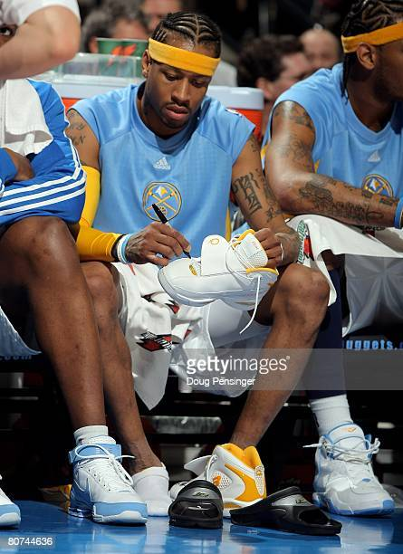 Allen Iverson of the Denver Nuggets autographs his shoes after leaving the game the Memphis Grizzlies and then giving them to fans at the Pepsi...