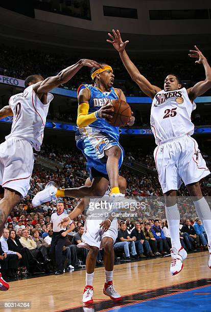 Allen Iverson of the Denver Nuggets drives the lane against Andre Iguodala and Rodney Carney of the Philadelphia 76ers on March 19 2008 at the...
