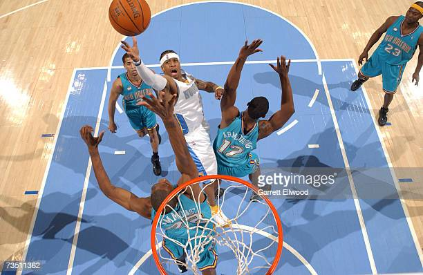 Allen Iverson of the Denver Nuggets goes to the basket against Hilton Armstrong and Cedric Simmons of the New Orleans/Oklahoma City Hornets at the...