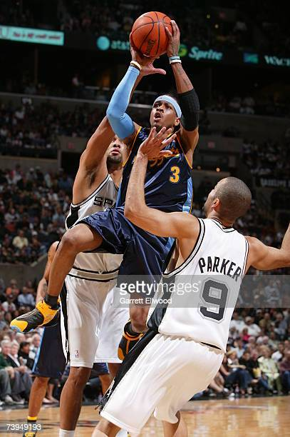 Allen Iverson of the Denver Nuggets goes to the basket against Tim Duncan and Tony Parker of the San Antonio Spurs in Game One of the Western...