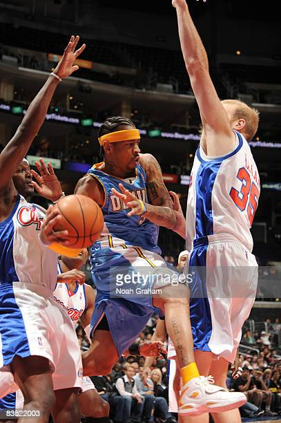 Allen Iverson of the Denver Nuggets goes up to make a pass between Al Thornton and Chris Kaman of the Los Angeles Clippers at Staples Center on...