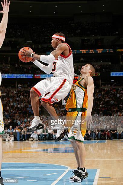 Allen Iverson of the Denver Nuggets looks to pass midair against Luke Ridnour of the Seattle SuperSonics during the game at the Pepsi Center on March...