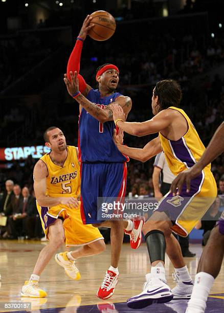 Allen Iverson of the Detroit Pistons passes the ball between Sasha Vujacic and Jordan Farmar of the Los Angeles Lakers on November 14 2008 at Staples...
