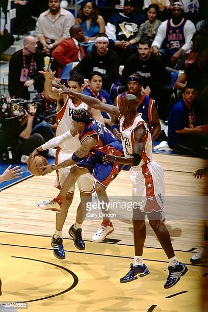 Allen Iverson of the Eastern Conference AllStars passes against Tim Duncan and Kevin Garnett of the Western Conference AllStars during the 2004...