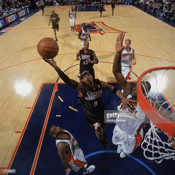 Allen Iverson of the Philadelphia 76ers covered by Adonal Foyle of the Golden State Warriors goes up for the shot during the game at The Arena in...