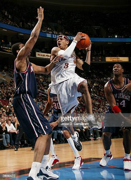 Allen Iverson of the Philadelphia 76ers drives against Jason Collins and Rodney Rogers of the New Jersey Nets January 9 2004 at the Wachovia Center...