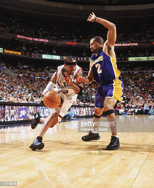 Allen Iverson of the Philadelphia 76ers drives around Derek Fisher of the Los Angeles Lakers at First Union Center on December 20 2002 in...
