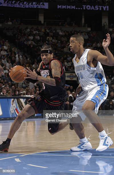 Allen Iverson of the Philadelphia 76ers drives by Andre Miller of the Denver Nuggets during the game at the Pepsi Center on February 17 2004 in...