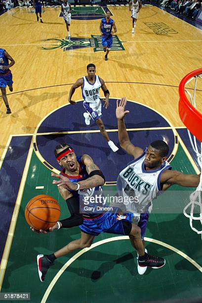 Allen Iverson of the Philadelphia 76ers drives for a layup against Desmond Mason of the Milwaukee Bucks during the NBA game at the Bradley Center on...