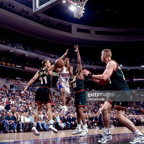 Allen Iverson of the Philadelphia 76ers drives to the basket against Detlef Schrempf of the Seattle Supersonics during a 1997 NBA Game played at the...