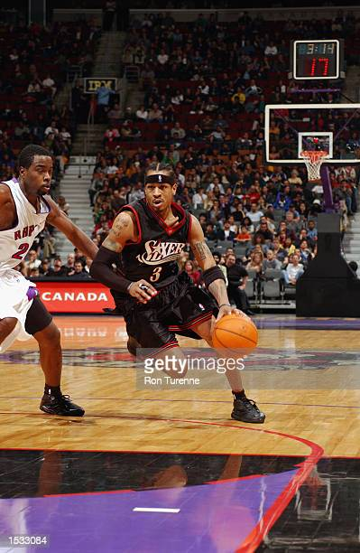 Allen Iverson of the Philadelphia 76ers drives to the basket past Alvin Williams of the Toronto Raptors during a preseason game on October 13 2002 at...