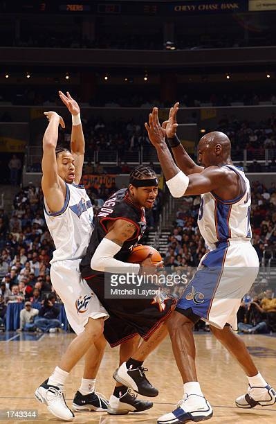 Allen Iverson of the Philadelphia 76ers gets caught as he drives between Tyronn Lue and Michael Jordan of the Washington Wizards during the game at...