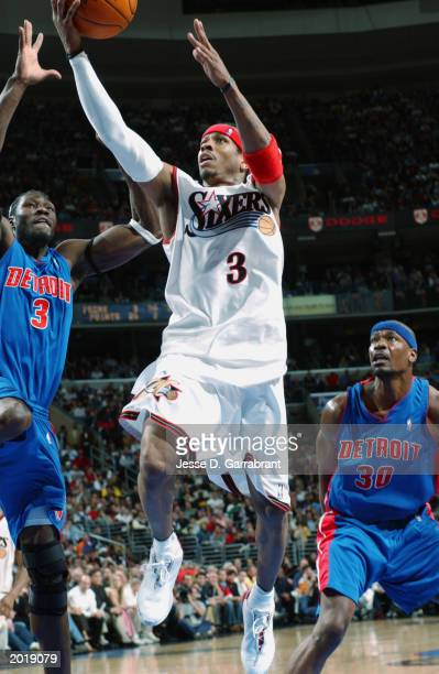 Allen Iverson of the Philadelphia 76ers goes for a layup past Ben Wallace and Clifford Robinson of the Detroit Pistons in Game six of the Eastern...
