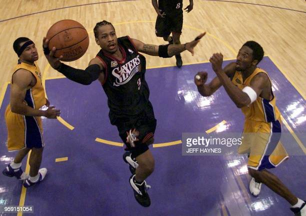 Allen Iverson of the Philadelphia 76ers goes in for a lay-up between Derek Fisher and Kobe Bryant of the Los Angeles Lakers 06 June, 2001 during the...