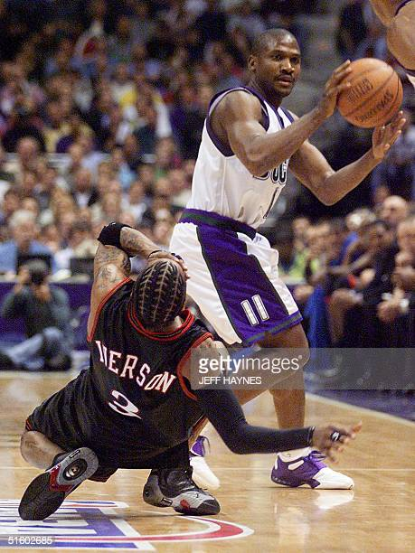 Allen Iverson of the Philadelphia 76ers goes over backwards after getting hit by Lindsay Hunter of the Milwaukee Bucks during game six of their NBA...
