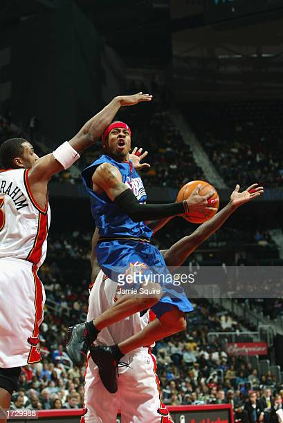 Allen Iverson of the Philadelphia 76ers goes to the basket while being confronted by Shareef AbdurRahim of the Atlanta Hawks during the game at...