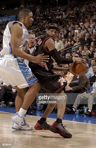 Allen Iverson of the Philadelphia 76ers is covered by Andre Miller of the Denver Nuggets during the game at the Pepsi Center on February 17 2004 in...