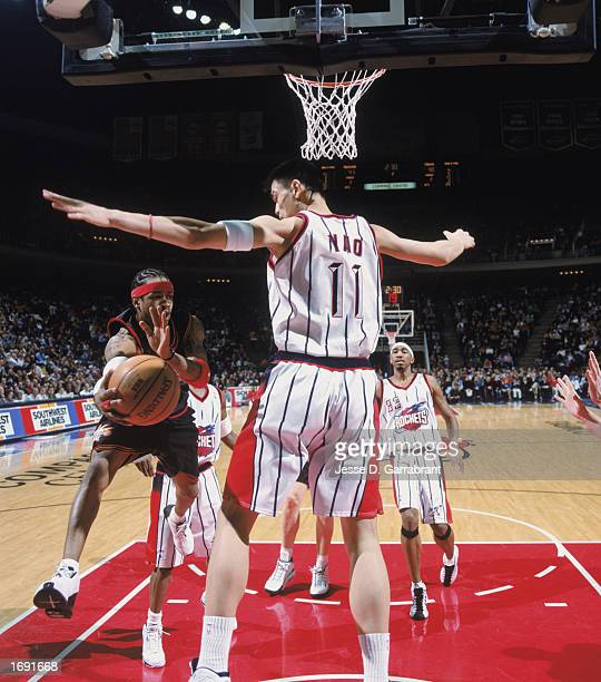 Allen Iverson of the Philadelphia 76ers keeps the ball in play against Yao Ming of the Houston Rockets at COMPAC Center on December 7 2002 in Houston...