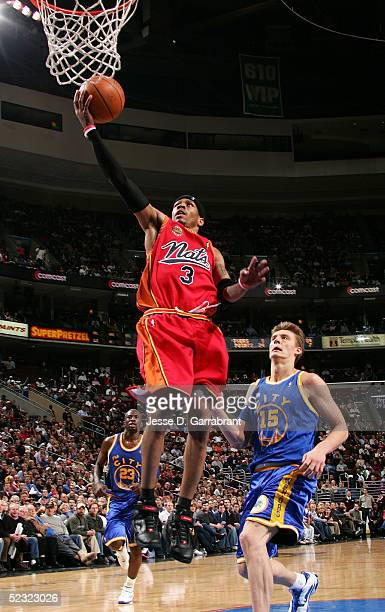 Allen Iverson of the Philadelphia 76ers lays one up past Andris Biedrins of the Golden State Warriors on March 8 2005 at the Wachovia Center in...
