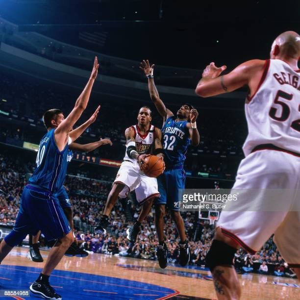 Allen Iverson of the Philadelphia 76ers looks to pass against Eddie Robinson and Brad Miller of the Charlotte Hornets in Game Three of the Eastern...