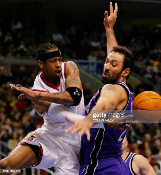 Allen Iverson of the Philadelphia 76ers passes around the back of Vlade Divac of the Sacramento Kings beneath the basket in the 1st period of their...