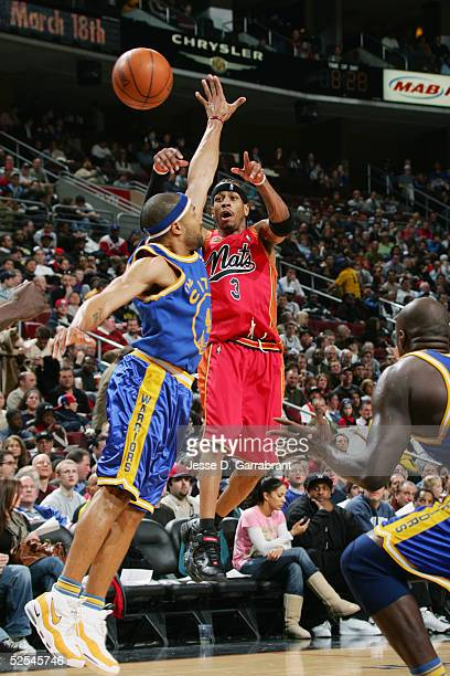 Allen Iverson of the Philadelphia 76ers passes over Derek Fisher of the Golden State Warriors during the game on March 8 2005 at the Wachovia Center...