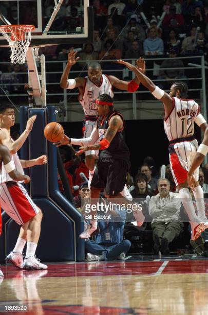 Allen Iverson of the Philadelphia 76ers passes the ball as he drives to the basket during the NBA game against the Houston Rockets at Compaq Center...