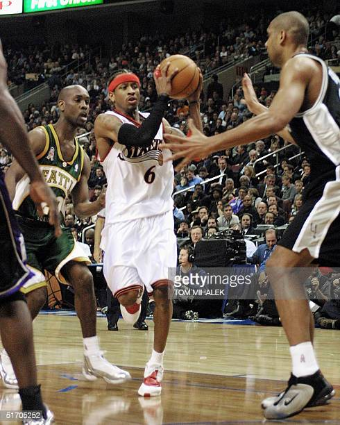 Allen Iverson of the Philadelphia 76ers playing on the East All Stars drives past Gary Payton of the Seattle SuperSonics and towards Tim Duncan of...