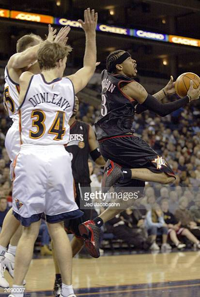 Allen Iverson of the Philadelphia 76ers shoots over Mike Dunleavy and Brain Cardinal of the Golden State Warriors during an NBA game at the Arena in...
