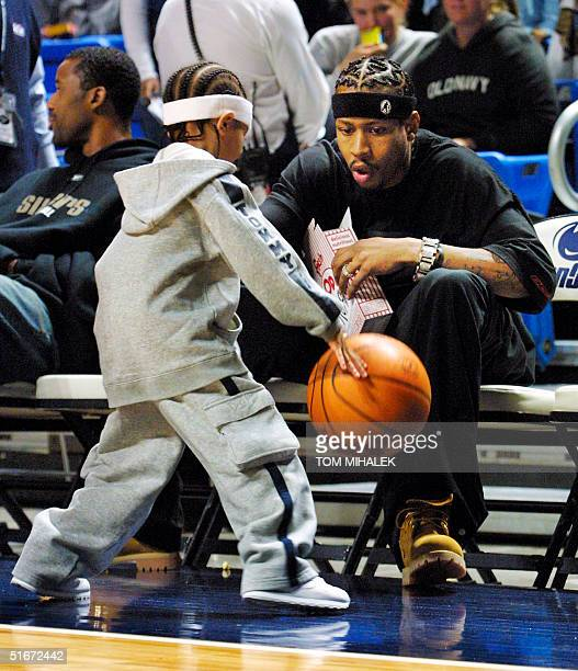 Allen Iverson of the Philadelphia 76ers watches as his son Allen Deuce Iverson bounces a basketball near the team's bench prior to the start of a...