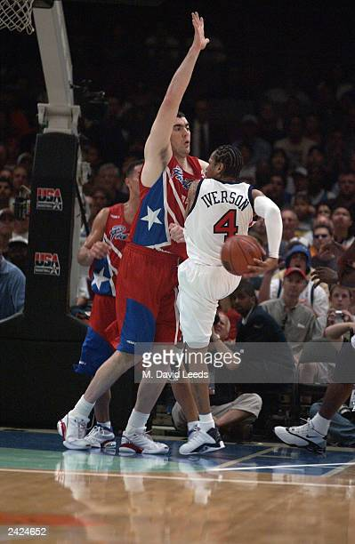 Allen Iverson of the USA makes a behind the back pass as he runs into the defense of Daniel Santiago of Puerto Rico during an exhibition game on...