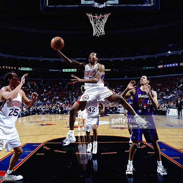 Allen Iverson#3 of the Philadelphia 76ers shoots a reverse layup under the basket against of the Toronto Raptors at the First Union Center during the...