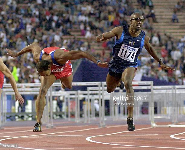 Allen Johnson of the US wins the men's 110M hurdles final ahead of Anier Garcia of Cuba at the 8th World Championships in Athletics 09 August 2001 in...
