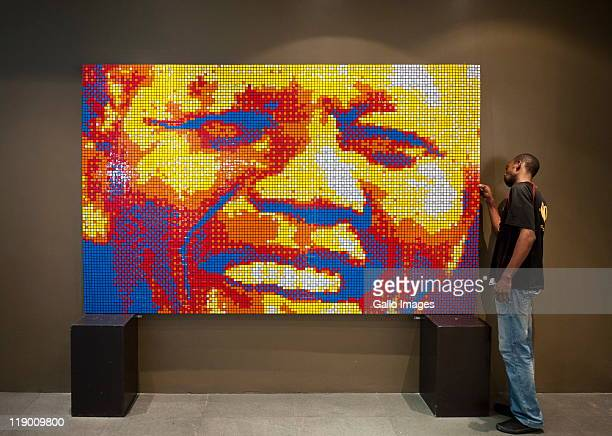 Allen Manongwa inspects a mosaic portrait of former South African President Nelson Mandela made entirely out of Rubik's Cubes by Jan Du Plessis...