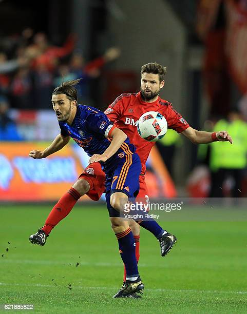 Allen of New York City FC is tackled by Drew Moor of Toronto FC during the first half of an MLS Conference semifinal playoff game at BMO Field on...