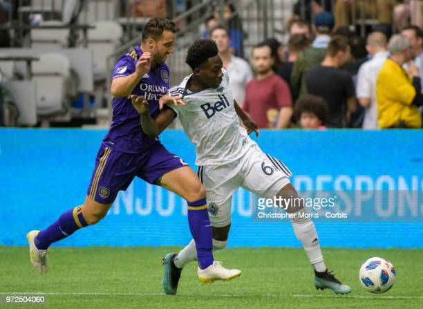 Allen of Orlando City and Alphonso Davies of the Vancouver Whitecaps fight for the ball at BC Place on June 9 2018 in Vancouver Canada