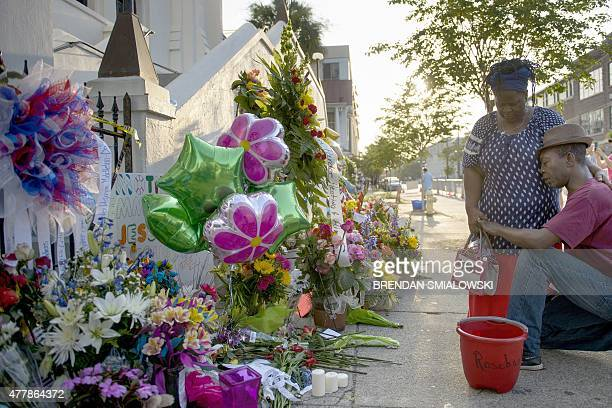 Allen Sanders pauses with his wife Georgette Sanders after placing flowers at a memorial outside Emanuel AME Church June 20, 2015 in Charleston,...