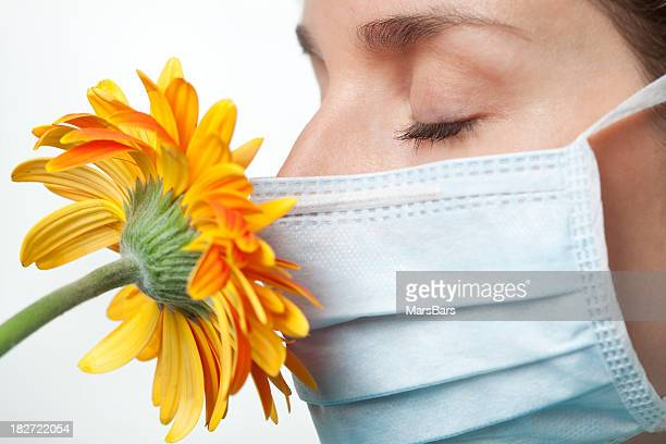 Allergies, smelling flower with surgical mask