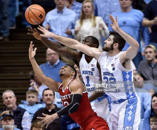 Allerik Freeman of the North Carolina State Wolfpack shoots against Theo Pinson and Luke Maye of the North Carolina Tar Heels during their game at...