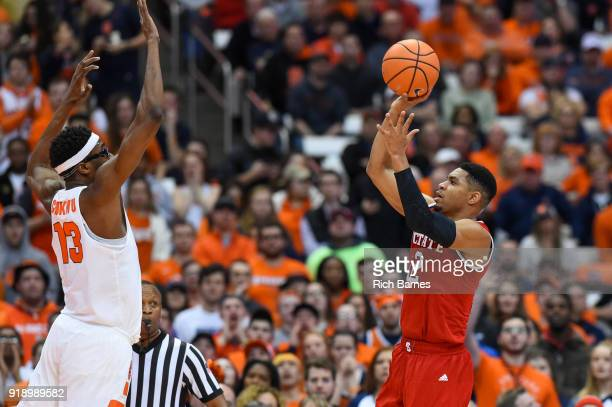 Allerik Freeman of the North Carolina State Wolfpack shoots the ball against the defense of Paschal Chukwu of the Syracuse Orange during the first...