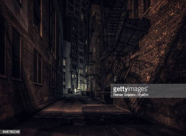 alley amidst buildings at night - alley stock photos and pictures