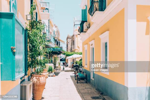 alley amidst houses against clear sky during sunny day - symi foto e immagini stock