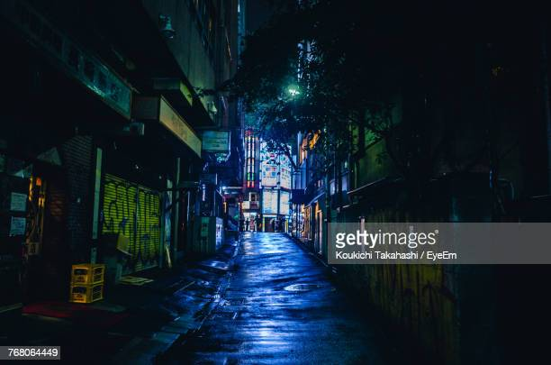 alley amidst illuminated city at night - alley stock pictures, royalty-free photos & images