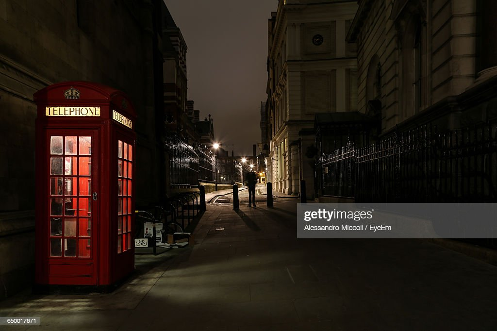 Alley By Telephone Booth Amidst Buildings At Night : Stock Photo