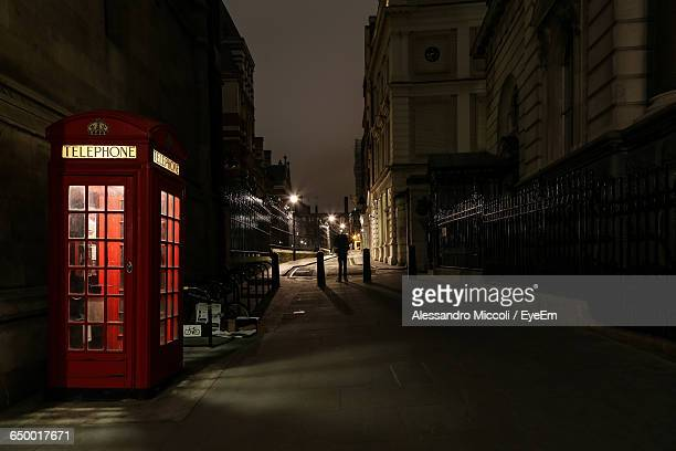 alley by telephone booth amidst buildings at night - alessandro miccoli stockfoto's en -beelden