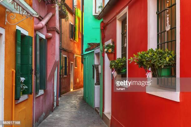 alley of colorful buildings of burano, venice, italy - burano foto e immagini stock