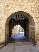 Alley or tunnel with architecture of an arch of medieval construction in the ancient neighborhood of the people of Calaceite in the province of Teruel, Aragón, Spain.