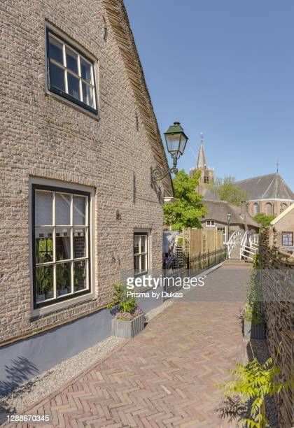 Alley with a footbridge towards the Bonifatius church, Noordeloos, Zuid-Holland.